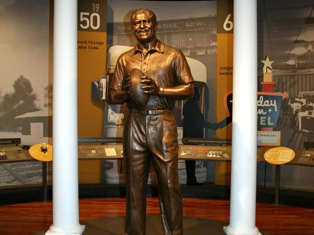 A bronze statue of Coach Rob stands in the cente of one of the exhibit rooms.
